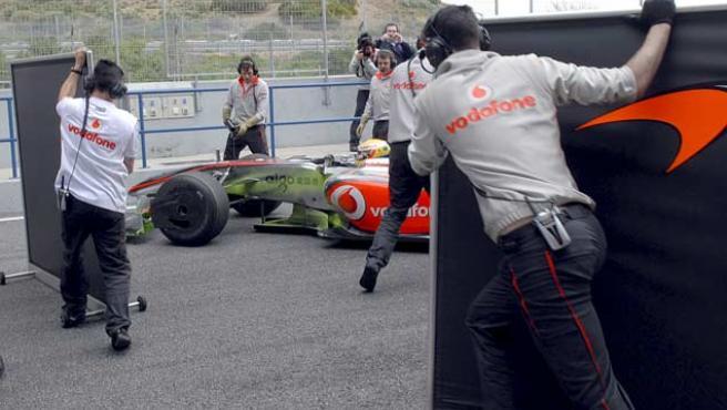 Los mecánicos de McLaren cubren a Lewis Hamilton en su llegada al box del equipo.