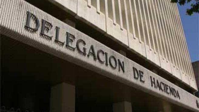 Dos personas pasean junto a la Delegación de Hacienda en Madrid.