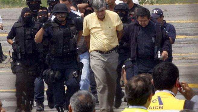 Policías federales escoltan a varios presuntos secuestradores de un avión de Aeroméxico en el Aeropuerto Internacional Benito Juárez de Ciudad de México.