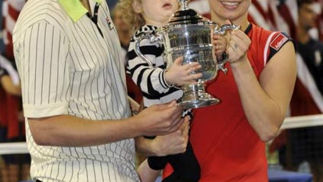 La tenista belga Kim Clijsters posa con el trofeo del US OPen en compañía de su marido, Brian Lynch, y su hija Jada.