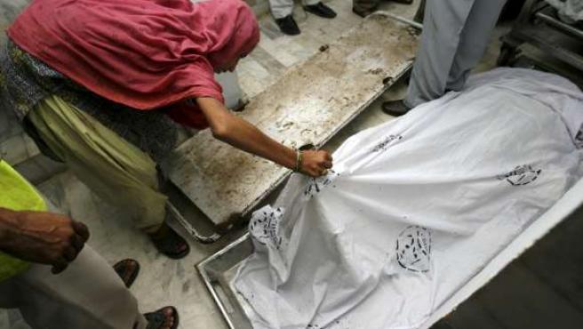 Una mujer observa uno de los cadáveres tras la estampida que ha provocado al menos la muerte de 18 mujeres.