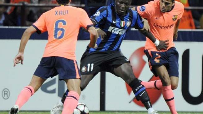 Los jugadores del FC Barcelona Xavi Hernández (i) y Daniel Alves (d) disputan el balón con Sulley Muntari (C) del Inter de Milán.
