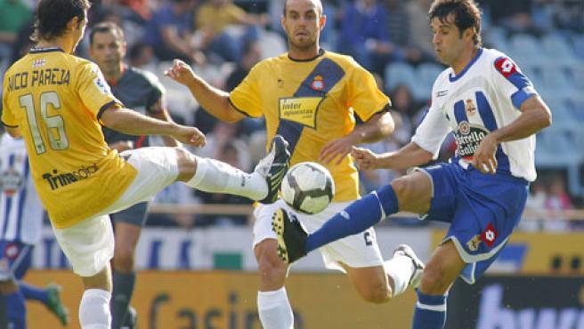 Juan Carlos Valerón (d), del Deportivo, intenta llevarse la pelota ante la presión de los jugadores del RCD Espanyol Moisés Hurtado (c) y Nico Pareja.