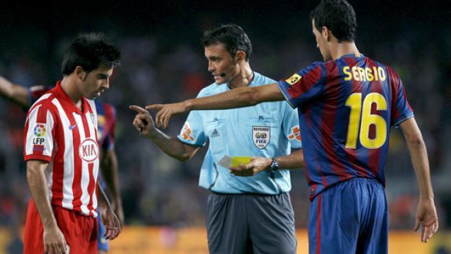 El árbitro Mejuto González (c) conversa con Jurado (i), del Atlético de Madrid, en presencia del barcelonista Busquets.