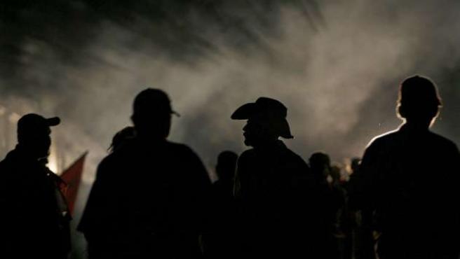 Seguidores del presidente hondureño depuesto, Manuel Zelaya, permanecen ante la embajada brasileña donde se refugia mientras la Polcía lanza gases lacrimógenos.