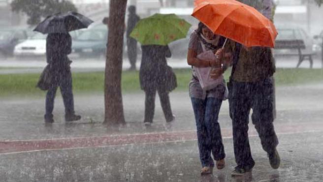 Varias personas se protegen de la lluvia.