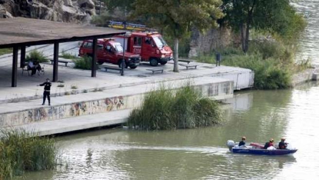 Miembros del Cuerpo de Bomberos del parque de Toledo rastrean el río Tajo junto al antiguo atracadero de piraguas.