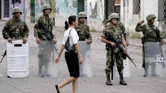 Una mujer pasa cerca de soldados en los alrededores de la embajada de Brasil en Tegucigalpa.