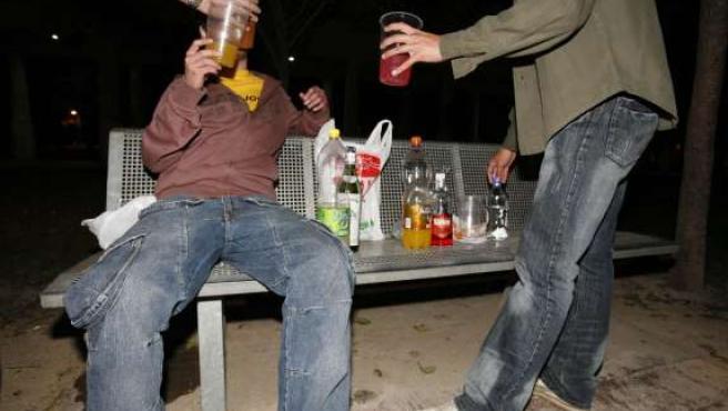 Tres jóvenes toman unas copas en una típica noche de botellón.