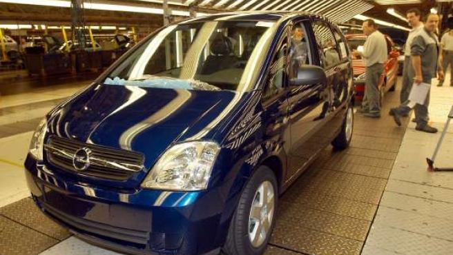 Varios operarios de la planta de Figueruelas, en Zaragoza, observan un vehículo casi terminado.