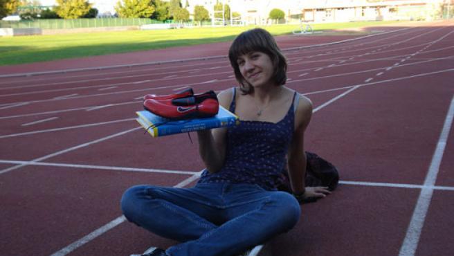 La atleta Natalia Romero, en la pista de entrenamiento de su club, el Caja Jaén, con un libro y sus zapatalilas.