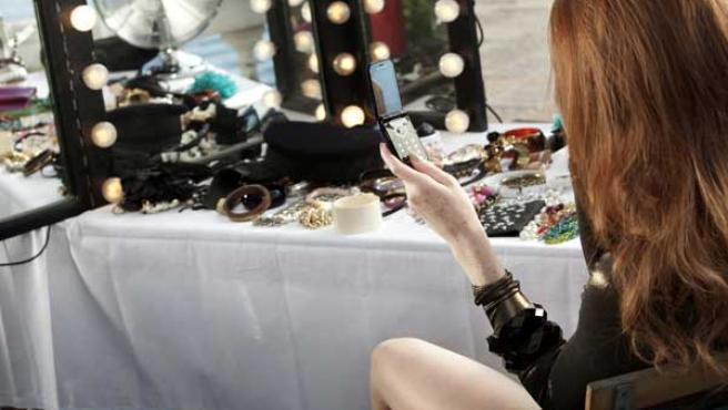 Una mujer mira la pantalla de su móvil.