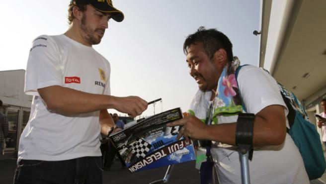 Fernando Alonso firma un autógrafo en Japón.