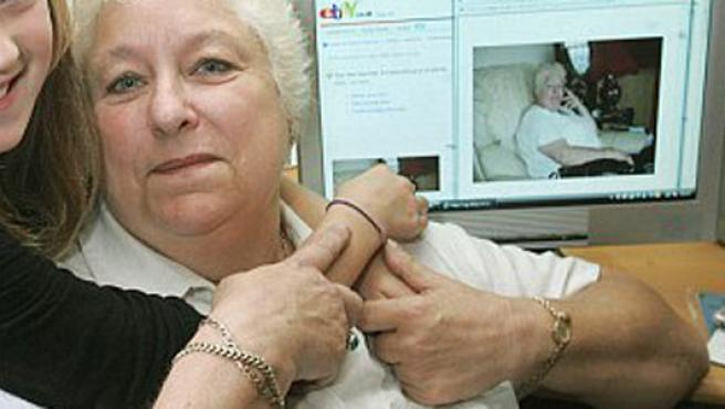 La niña abraza a su abuela, a quien, a modo de broma, intentó vender en Internet; detrás, en el ordenador, la imagen que se utilizó para el anuncio en eBay.