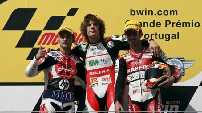El piloto italiano Marco Simoncelli de Gilera (centro) celebra su victoria junto al francés Mike Di Meglio (dcha) de Aprilia y español Héctor Barberá.
