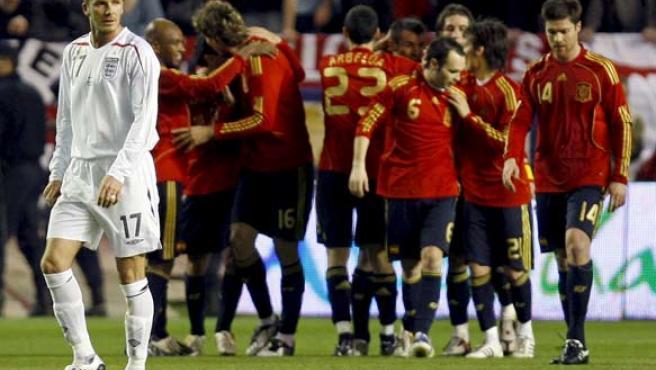 Los jugadores de la selección española celebran (al fondo) el segundo gol del partido, de Fernando Llorente (tercero izq.). Delante, un decepcionado David Beckham.