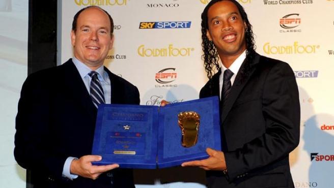 El jugador brasileño del AC Milan Ronaldinho (d) es premiado con el Golden Foot 2009 por el príncipe Alberto de Mónaco.