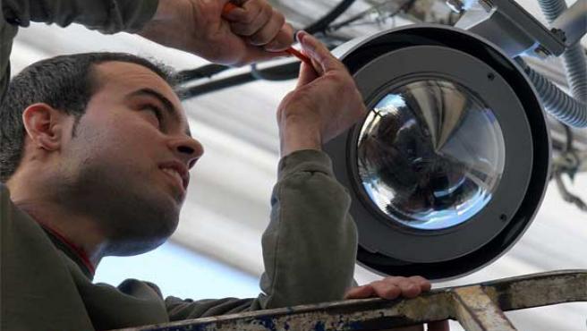 Un operario instala una cámara de videovigilancia.