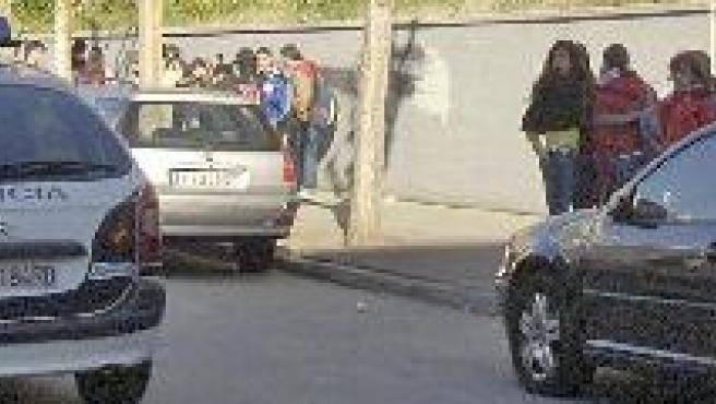 Un coche policial pasa frente a un centro escolar.