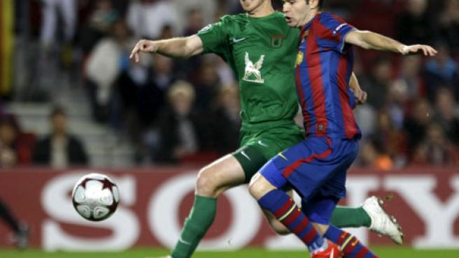 El barcelonista Andrés Iniesta (d) pelea con Cristian Ansaldi, del Rubin Kazan.
