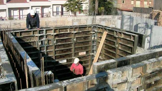 Unos obreros trabajan en la construcción de un refugio en el sótano de una vivienda.