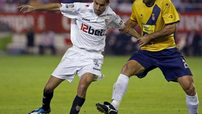 El extremo del Sevilla, Jesús Navas, protege el balón ante el jugador del Espanyol, Moises.