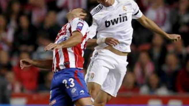 Pepe, defensa del Real Madrid, se anticipa de cabeza a David Barral, delantero del Sporting.