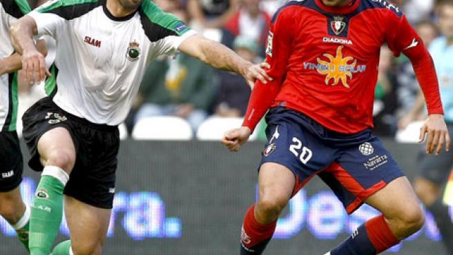 El delantero de Osasuna Aranda (d) controla el balón ante la presión defensiva del central del Racing Marc Torrejón.