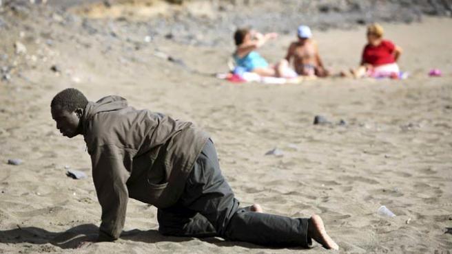 """""""EL PARAÍSO ESPAÑOL"""". Esta foto, tomada en mayo de 2006, y que retrata el esfuerzo físico de un inmigrante que llegó en patera a las islas Canarias, ante la indiferencia de los bañistas, está incluida dentro de la colección Las fotografías de la década de la agencia Reuters."""