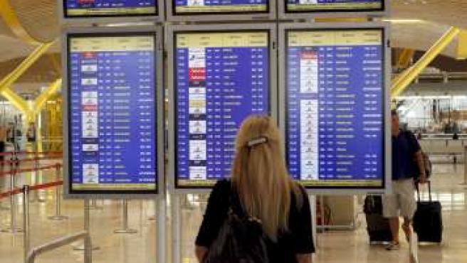 Una joven comprueba este martes la salida de su vuelo en la T-4 de Barajas.