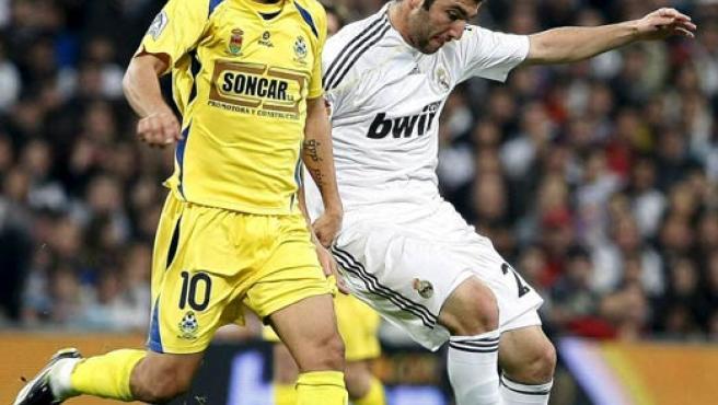 El delantero argentino del Real Madrid, Gonzalo Higuaín (d) pelea un balón ante el centrocampista del Alcorcón Sergio Mora (i).