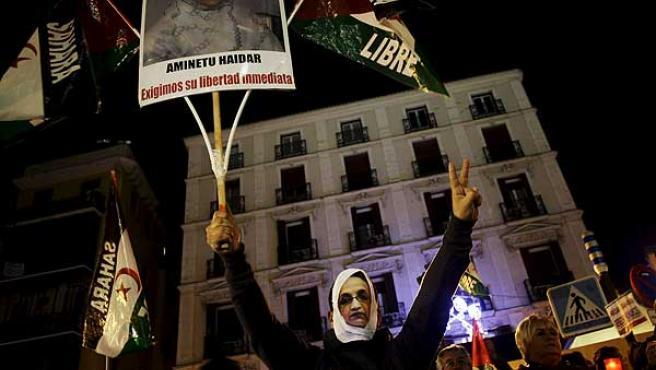 Un manifestante con una máscara de Aminatu Haidar, durante la marcha en Madrid para pedir una solución al caso de la activista.