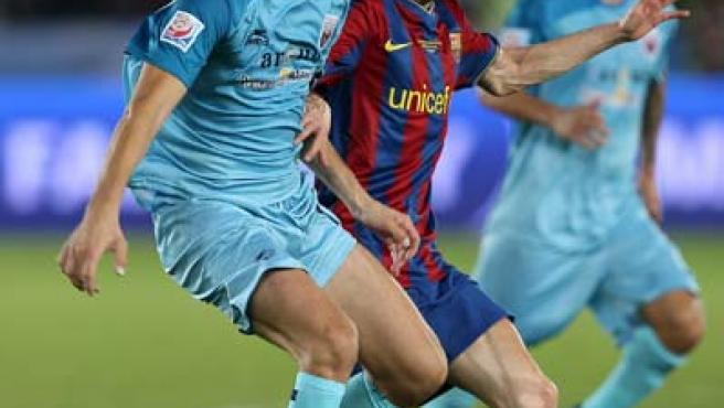 El jugador Andrés Iniesta (C), del FC Barcelona, disputa la bola con Santiago Solari (i) del Atlante FC.