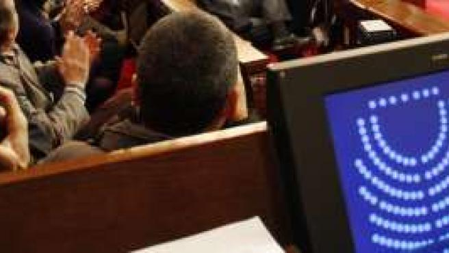 Vista del hemiciclo y una de las pantallas del Parlament catalán.