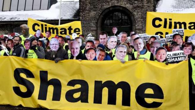 Activistas con caretas de algunos de los líderes asistentes a la cumbre del Cambio Climático se manifiestan en Copenhague.