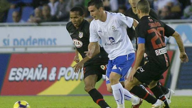 El delantero del Tenerife Alejandro Alfaro intenta deshacerse de la presión de dos jugadores del Atlético de Madrid, el brasileño Paulo Assunçao y el portugués Simao.