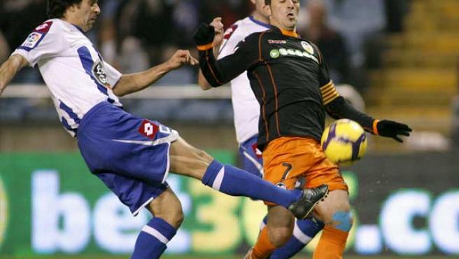 El delantero del Valencia, David Villa, disputa el balón con el centrocampista del Deportivo, Juan Carlos Valerón.