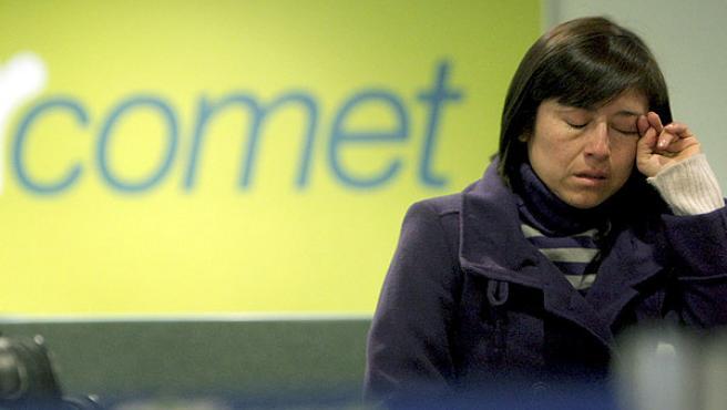 Una pasajera se lamenta junto a los mostradores de Air Comet en el aeropuerto de Barajas.