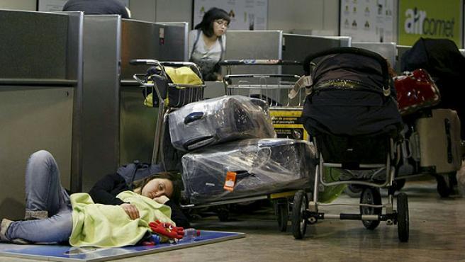 Pasajeros de Air Comet esperan con sus equipajes junto a los mostradores de facturación en Barajas.