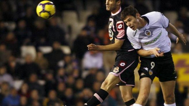 El valencianista Nikola Zigic (d) y el deportivista Adrián López luchan por cabecear un balón.