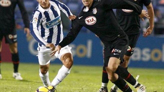 El jugador del Atlético de Madrid, Camacho (dcha), pelea por el control del balón con el jugador del Recreativo de Huelva, Pablo Sánchez.