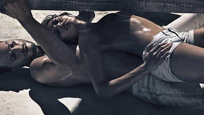 Una de las imágenes de la campaña con Eva Mendes y Jamie Dornan tumbados sobre la arena.