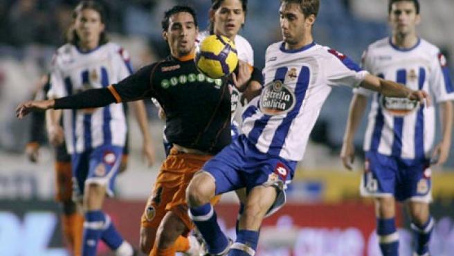 El centrocampista del Valencia, Vicente (izda), pelea por el control del balón con el jugador del Deportivo de la Coruña, Piscu.