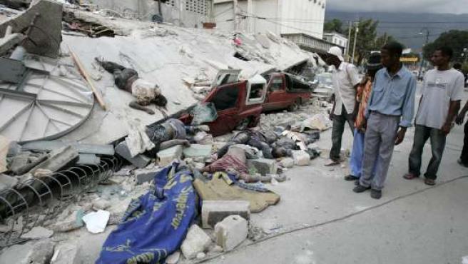 Unos hombres observan varios cuerpos entre los escombros de un edificio derrumbado, en el barrio Belair, en Puerto Príncipe (Haití).