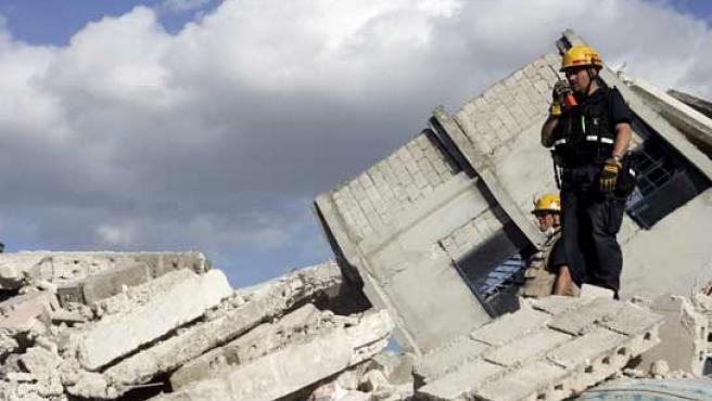 Un bombero encaramado a los cascotes de un edificio derrumbado por el seísmo en Haití.