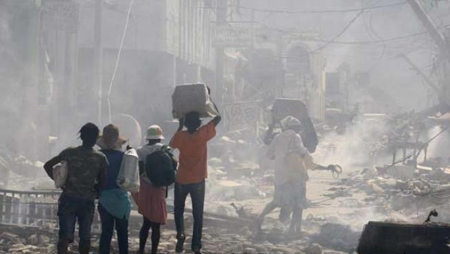 Varias personas deambulan por una calle de Puerto Príncipe.