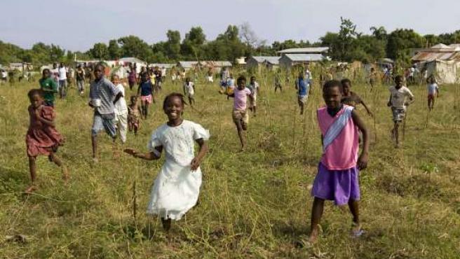 Un grupo de niños corre a recibir un helicóptero con ayuda humanitaria, a las afueras de Puerto Príncipe.