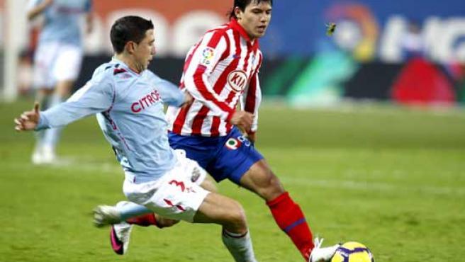 El delantero argentino del At. de Madrid, Kun Aguero (d), intenta llevarse el balón ante el jugador del Celta de Vigo, Roberto Lago.