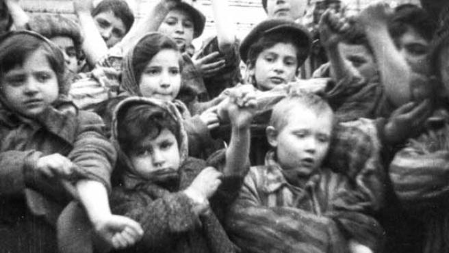 Varios niños que sobrevivieron al campo de Auschwitz muestran sus tatuajes identificativos.