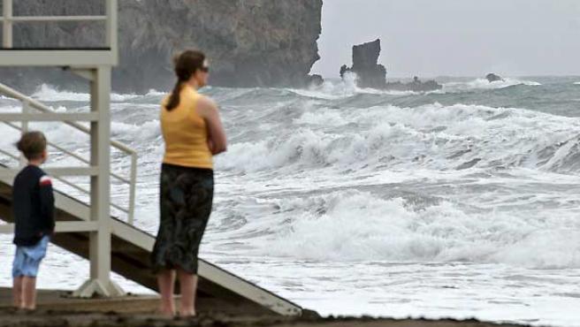 Una mujer y su hijo observan las grandes olas formadas en la playa de Gran Tarajal, en Fuerteventura.